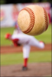 Baseball close up, pitcher in background representing character quality of vision