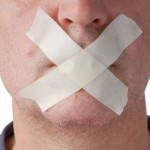 """Man's mouth covered with tape in an """"X"""" representing online reputation"""