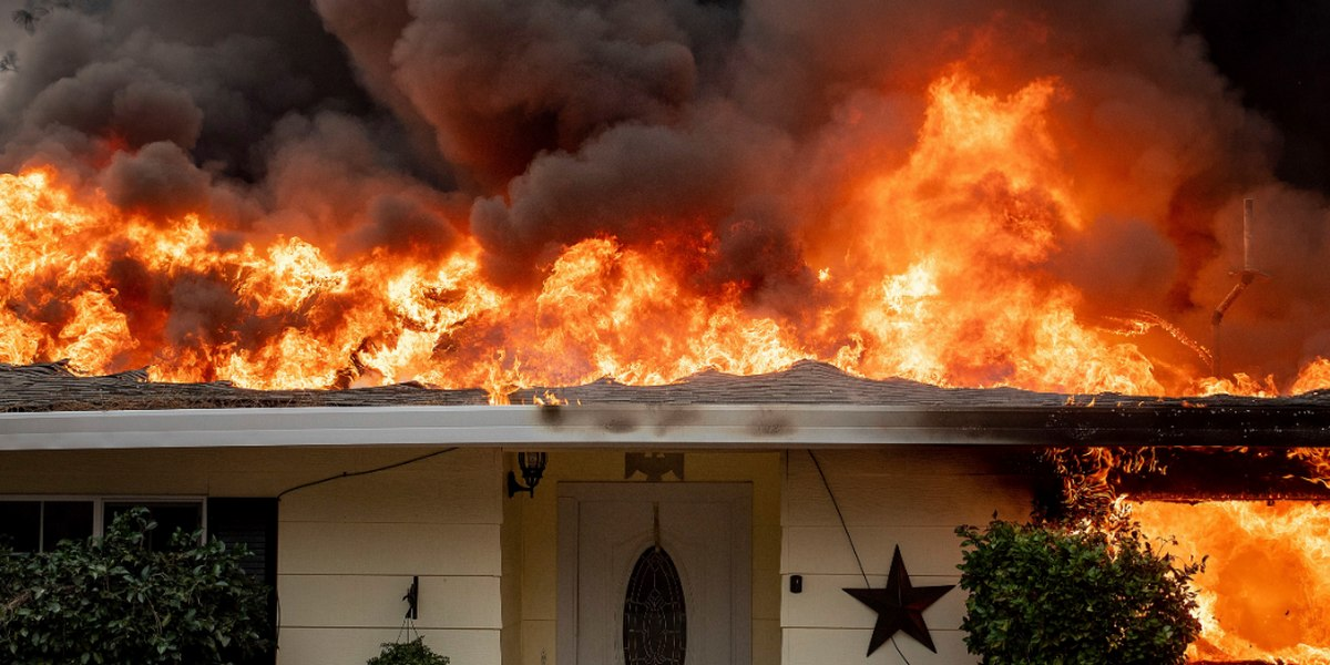 Wildfire burning home roof on fire